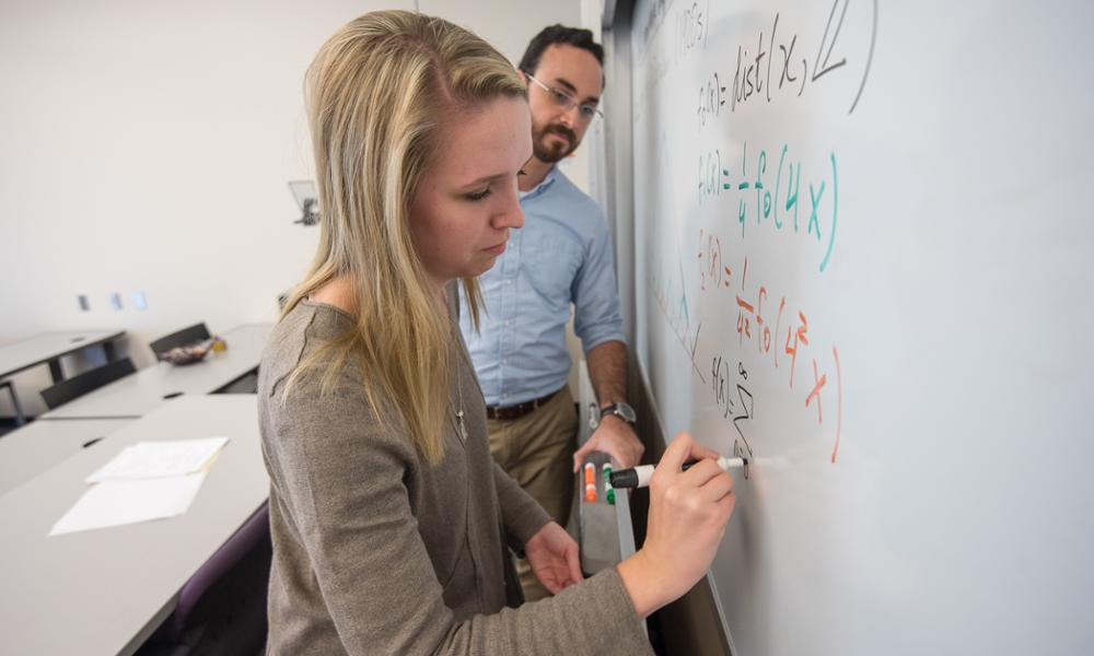 student and professor working on a white board